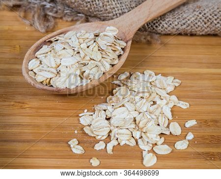 Uncooked Rolled Oats In The Wooden Spoon And Scattered Beside On The Bamboo Wooden Cutting Board, Cl