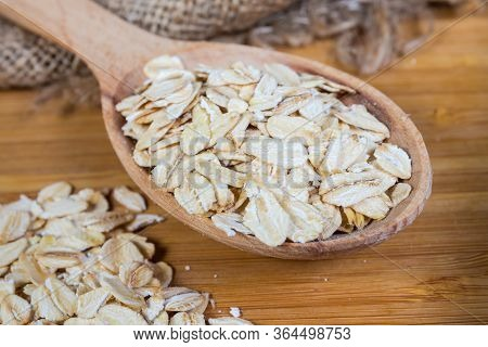 Small Pile And Wooden Spoon Of Uncooked Rolled Oats On The Bamboo Wooden Cutting Board, Fragment Clo