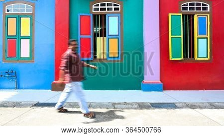 SINGAPORE - DECEMBER 31, 2019: Street scene from Little India district in Singapore. Woman walks past colourful House of Tan teng Niah (motion blur)