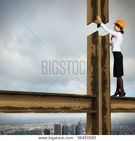 Business woman standing high over a cityscape