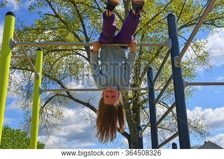 Adorable Little Girl Laughing Happily, Hanging Upside Down On Parallel Bars At Playground