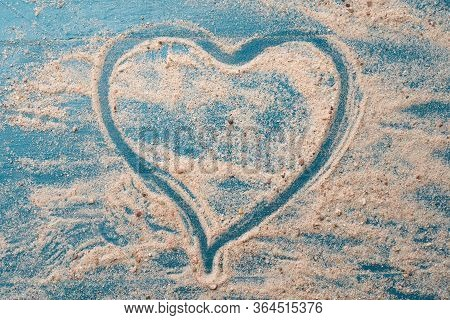 Golden Beach Sand With Heart Shape On A Blue Wood Background. Summer Travel Love Concept Backdrop.