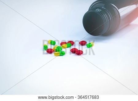 Red Tablets And Green-yellow Capsule Pills With Amber Plastic Bottle On White Table. Pharmaceutics C