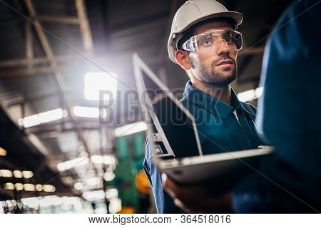 Industry Maintenance Engineer Wearing Uniform And Safety Helmet Under Inspection And Checking Produc