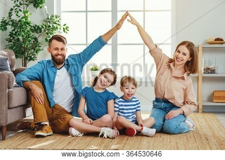 Cheerful Young Family Man And Woman Forming Rooftop With Hands While Sitting With Little Kids On Flo