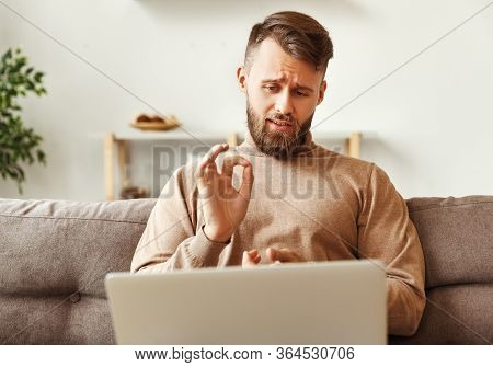 Serious Young Man In Casual Clothes Working From Home During Coronavirus Talking To Colleague And Sh