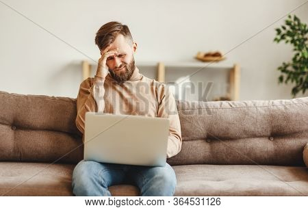 Discontent Young Male In Casual Wear Sitting On Sofa And Reading Bad News On Laptop While Spending T