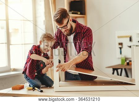 Delighted Little Boy In Casual Clothes Laughing And Helping Father To Drill Hole While Assembling Fu