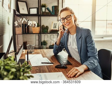 Positive Successful Young Businesswoman In Glasses And Formal Wear Talking On Mobile Phone And Discu