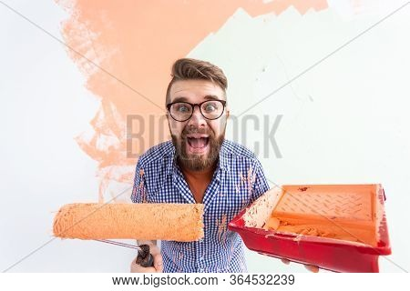 Funny Man Painting Interior Wall With Paint Roller In New House. Guy With Roller Applying Paint On A