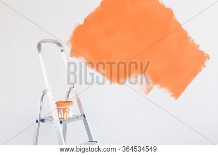Ladder With Paint In Bucket Near Color Wall Indoors. Renovation And Redecoration Concept. Copy Space