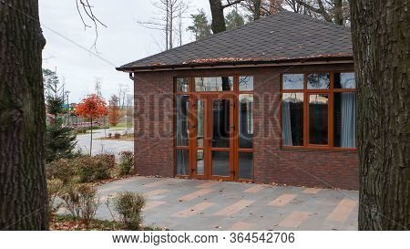 Ukraine, Bucha - October 20, 2019: A Large Stylish House Made Of Brown Stone, Large Windows And A Hu