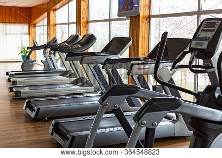 Exercise Machines For Running Stand In A Row In The Gym With Panoramic Windows. Daylight, Selective