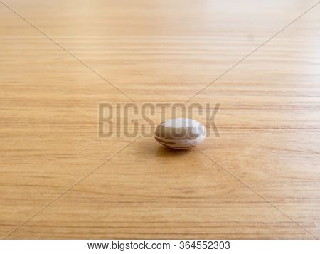 A Grain Of Carioca Beans Isolated, On Wooden Texture Table.