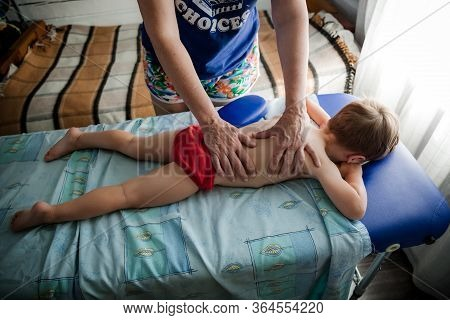 Doctor Osteopath Massage Therapist Is Doing Massage To A Little Boy. Hands Massage The Back And Cerv