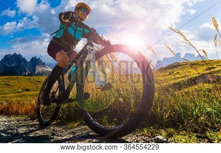 Cycling outdoor adventure in Dolomites. Cycling woman in Dolomites landscape. Woman cycling MTB enduro trail track. Outdoor sport activity.