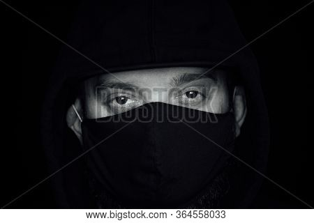 A Man Wearing A Black Respiratory Mask On His Face. A Man In The Street In A Black Mask. Virus. Coro