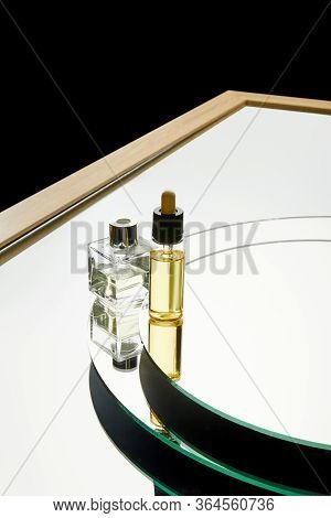 High Angle View Of Aromatic Perfume Bottle And Serum Bottle On Mirror Surface Isolated On Black