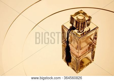 High Angle View Of Aromatic Perfume Bottle On Round Mirror Surface With Reflection