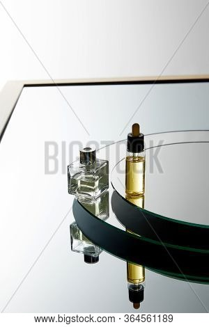 High Angle View Of Perfume Bottle And Serum Bottle On Mirror Surface