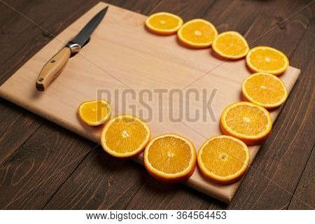 Fresh orange sliced fruits on a wooden table and cutting board with kitchen knife. Natural and healthy food. Arranged as a frame with blank space in center.
