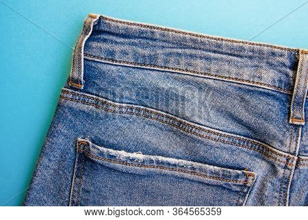 Jeans On A Blue Background. Jeans Elements, Pockets, Seams In Close-up. Ripped Jeans. Copy Space