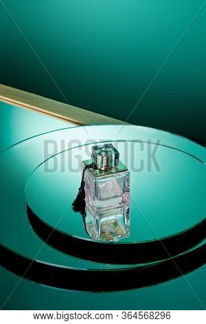High Angle View Of Purple Perfume Bottle On Green Round Mirror Surface