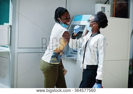 Two African Womans Wearing Disposable Medical Mask And Gloves Near Atm Cash During Coronavirus Pande