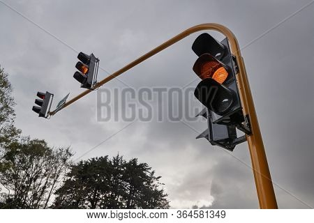 Overhead traffic lights at an intersection, yellow light changing
