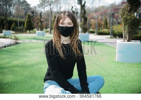 Girl With Dreadlocks In A Black Protective Mask From Coronavirus With Eyes Wide Open In A Park On A