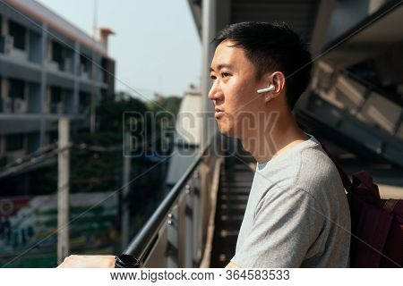 Close Up Of Young Man Listening To Music With Wireless Earpods While Commuting By Train At Station.
