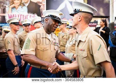 MAY 22 2019-NEW YORK: USMC officer shakes hands with a Corpsman after a group photo on the red steps in Father Duffy Square during Fleet Week in Manhattan on May 22, 2019.