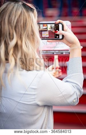 MAY 22 2019-NEW YORK: A woman takes a cellphone picture of U.S. Marines on the iconic red steps in Father Duffy Square for Fleet Week in Manhattan on May 22, 2019.