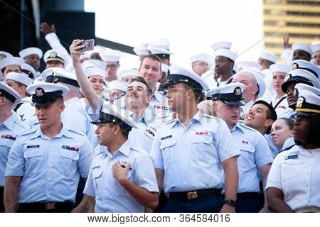 MAY 22 2019-NEW YORK: A Coast Guardsmen takes a cellphone selfie with others on the iconic red steps in Father Duffy Square for Fleet Week in Manhattan on May 22, 2019.