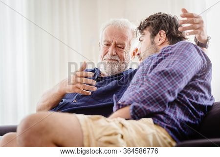Old Man Serious Discussion With Younger Man Indoor, Grand Father Serious Talking With His Son At Hom