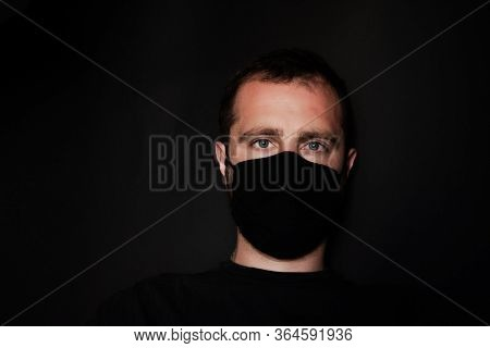 Young Guy On Black Background In Protective Mask. A Guy With Black Hair And A Black Face Mask Agains