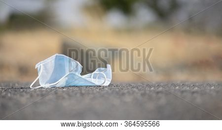 Discarded Medical Face Mask Stuck Into Road - Concept Of Unhygienic Dispose Of Masks Helps To Spread