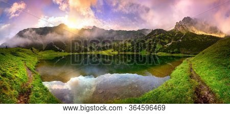 Magnificent Sunrise At A Lake In The Alps With Mountains, Colorful Clouds And Wafts Of Mist Reflecte