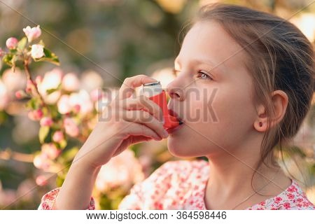 Little Girl Having Asthma Using Asthma Inhaler Due To Pollen Allergy - Shallow Depth Of Field