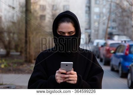 Young Girl In City Street Wearing Black Sterile Medical Face Mask. Woman Using The Phone To Search F