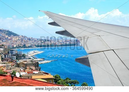Traveling concept. Aerial view of Naples and Mediterranean sea, Italy. Looking Out the Window of a Plane. Scenic view with wing of an airplane