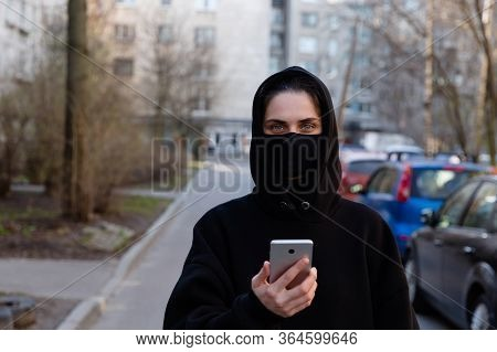 Woman In Protective Black Mask Holding A Smartphone Outside During Coronavirus Covid-19 Epidemic