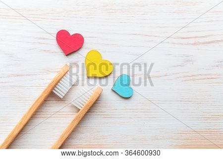 Two Bamboo Toothbrushes And Three Wood Hearts On Vintage Wood Background. Biodegradable Bamboo Tooth