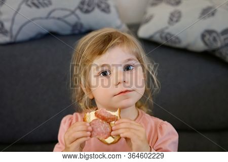Adorable Little Toddler Girl Eating Fresh Prepared Salami Sandwith In Kitchen. Happy Child Eats Heal