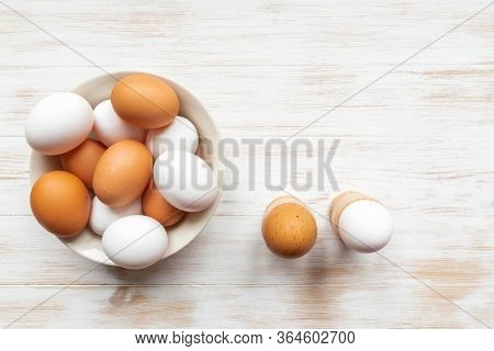 Bowl With Brown And White Chicken Eggs And Boiled Eggs In Holders On Table. Eggs In Plate And Holder