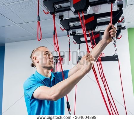 Physiotherapy. Suspension Training Therapy. Young Man Doing Fitness Traction