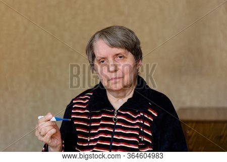 Elderly Woman With Thermometer. Female Hands Holding A Digital Thermometer. Concept Of Fever, Flue O