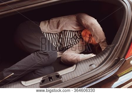 Hostage In The Car Trunk. Theft And Human Trafficking. A Woman Is Lying In A Car. Fear And Horror. K