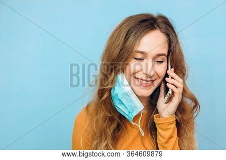 A Pretty Girl On The Phone In A Medical Mask. Portrait Of A Close-up Of A Girl On A Blue Background.