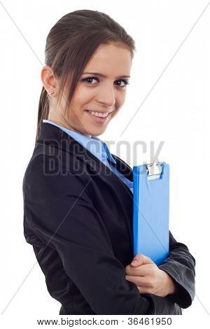 Side view of a young business woman holding a clipboard and smiling .Facing the camera. Isolated on white background